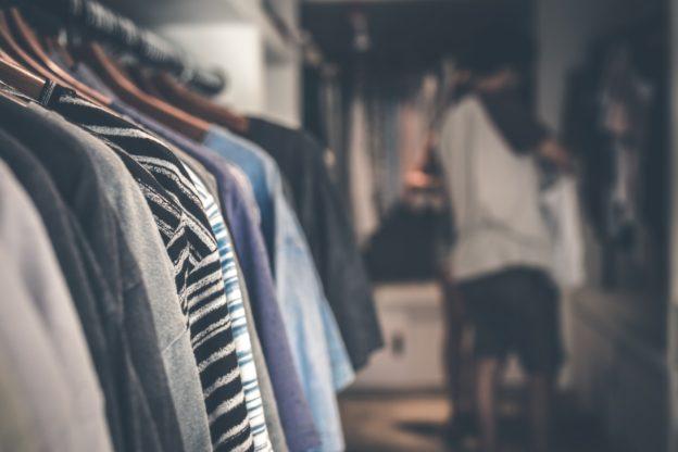 Person kigger på sit tøj i garderobe