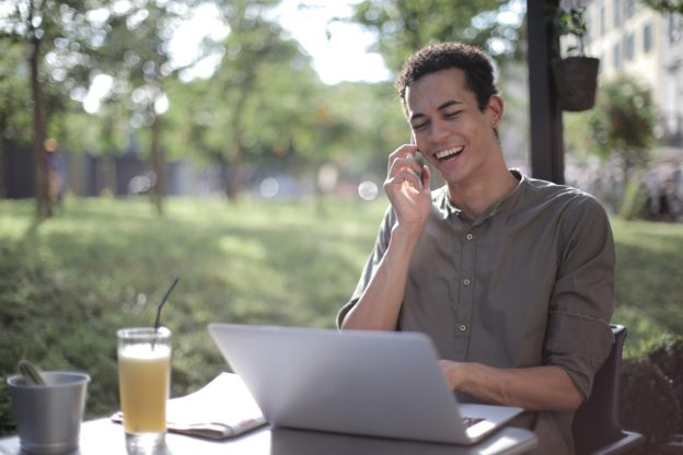 Mand taler i telefon med juice ved siden af