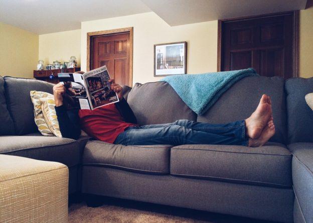 Person slapper af i sin sofa med en avis